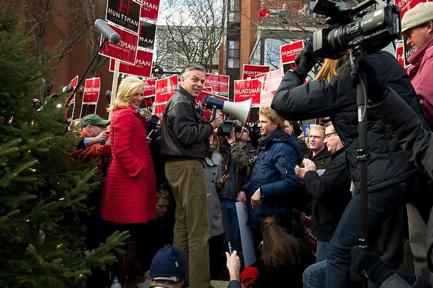 One day before the nation's first presidential primary of 2012, Republican presidential candidate and former Utah Governor Jon Huntsman is joined by his wife Mary Kaye as he addresses supporters with a bullhorn while balancing himself on boulders at Eagle Square in Manchester, N.H., Monday, January 9, 2012. (Rod Lamkey Jr/ The Washington Times)