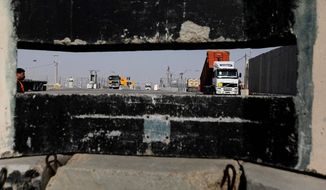 In this Monday, Dec. 19, 2011 photo, seen through a gun slit, trucks with goods destined for Gaza wait to be unloaded on the Israeli side of the Kerem Shalom crossing, between Israel and the Gaza Strip. Each day, dozens of trucks move food, consumer products and industrial materials into the Gaza Strip at this heavily fortified crossing, in an odd arrangement that has turned Israel into a key supplier to a territory governed by its bitter enemy Hamas. (AP Photo/Tsafrir Abayov)