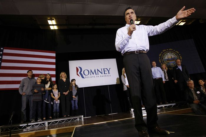 With his family behind him, former Massachusetts Gov. Mitt Romney campaigns for the Republican presidential nomination at McKelvie Intermediate School in Bedford, N.H., on Monday, Jan. 9, 2012. (AP Photo/Charles Dharapak)