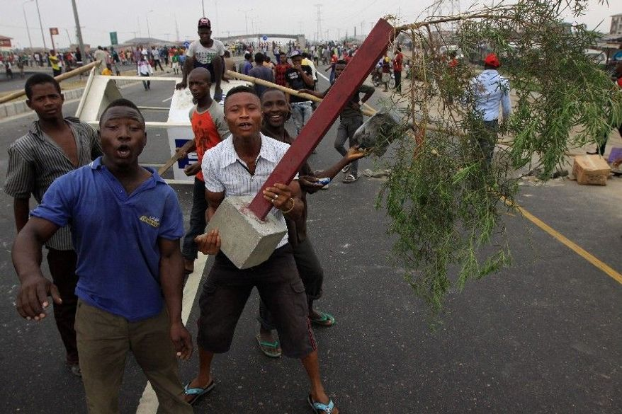 """Youths in Lagos, Nigeria, take to the street Wednesday, the third day of a nationwide strike called """"Occupy Nigeria"""" following removal of a more-than-two-decade-old fuel subsidy. At least 10 people have been killed in demonstrations over rising fuel prices and government corruption. The national government warned of """"anarchy."""" (Associated Press)"""