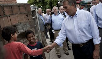 Speaker of the House Rep. John Boehner, R-Ohio, front right, shakes hands with a boy during a visit to the Vidigal slum in Rio de Janeiro, Brazil, Monday, Jan. 9, 2012. Boehner toured a Rio de Janeiro shantytown that has recently been taken over from drug traffickers by police. Boehner is leading a seven-member congressional delegation to Brazil, Colombia, and Mexico. (AP Photo/Felipe Dana)