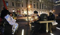Felix Rivera-Pitre (left), Ned Merrill (center) and Robert Segal try to stay warm Jan. 11, 2012, after spending the night at Zuccotti Park in New York. About 20 Occupy Wall Street protesters spent the night in the park after metal barricades surrounding it came down the day before. (Associated Press)