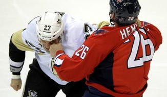 Washington Capitals left wing Matt Hendricks (26) fights with Pittsburgh Penguins right wing Craig Adams (27) during the first period of an NHL game, Wednesday, Jan. 11, 2012, in Washington. (AP Photo/Nick Wass)