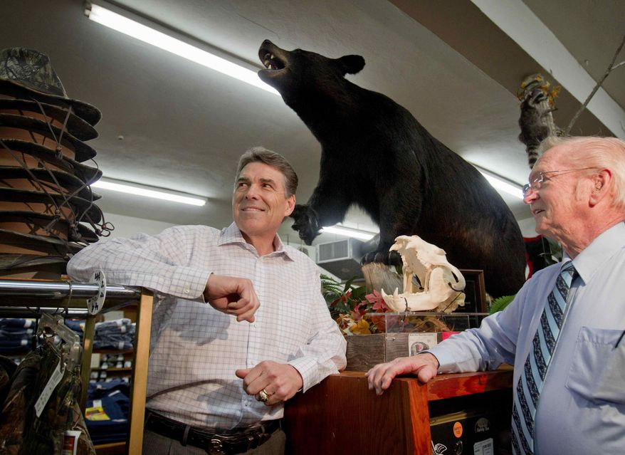 Texas Gov. Rick Perry (left) stands under a black bear killed by the son of Glenn Brock (right), owner of Brock's department store, during a stop on Mr. Perry's GOP presidential campaign on Monday, Jan. 9, 2012, in Pickens, S.C. (AP Photo/David Goldman)
