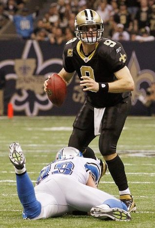 New Orleans Saints quarterback Drew Brees looks for a receiver as Detroit Lions defensive end Kyle Vanden Bosch pursues during the first half of the wild-card playoff football game Saturday, Jan. 7, 2012, in New Orleans. (AP Photo/Gerald Herbert)