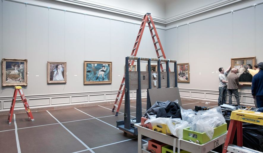 Handlers hang paintings in the National Gallery of Art's newly re-installed 19th-century French galleries. (Photograph courtesy National Gallery of Art)