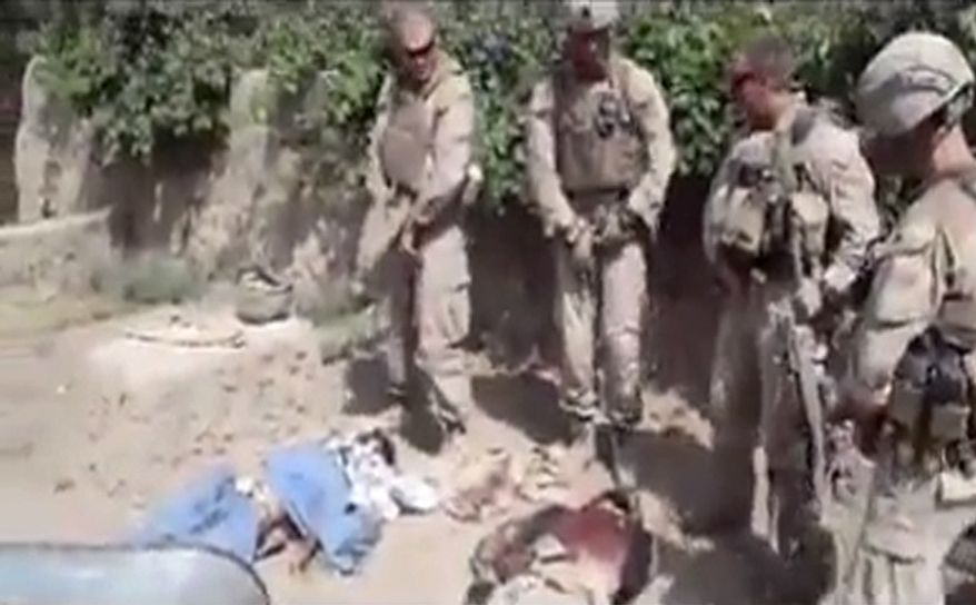 """**FILE** This image made on Jan. 12, 2012, from an undated video posted on the Internet by a YouTube user self-identified as """"semperfiLoneVoice"""" shows men in U.S. Marine combat gear standing in a semicircle over three bodies. U.S. Defense Secretary Leon E. Panetta branded as """"utterly despicable"""" the video purporting to show four U.S. Marines urinating on the corpses of Taliban fighters. (Associated Press)"""