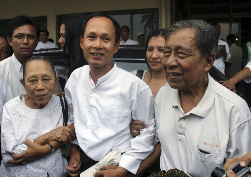 Pyone Cho (center), an activist of the 88 Generation Students Group, joins his parents upon his arrival at Yangon airport after released from a prison in Yangon, Myanmar. Myanmar freed some of its most famous political inmates Friday, sparking jubilation outside prison gates while signaling its readiness to meet Western demands for lifting economic sanctions. (Associated Press)