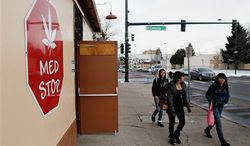 **FILE** Three young girls walk past the Med Stop marijuana dispensary in Denver, located across from Del Pueblo Elementary School, on Jan. 12, 2012. (Associated Press)