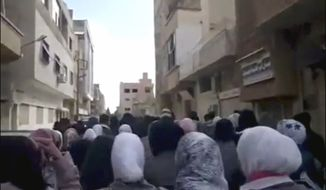 This image from amateur video made available by the Ugarit News group and shot Jan. 12, 2012, purports to show protesters demonstrating against the killing of a French journalist in Daraa, Syria. (Associated Press/Ugarit News Group via APTN)