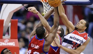 Washington Wizards center JaVale McGee battles for the ball against Philadelphia 76ers forward Elton Brand during the first half Saturday, Jan. 14, 2012, in Washington. (AP Photo/Nick Wass)