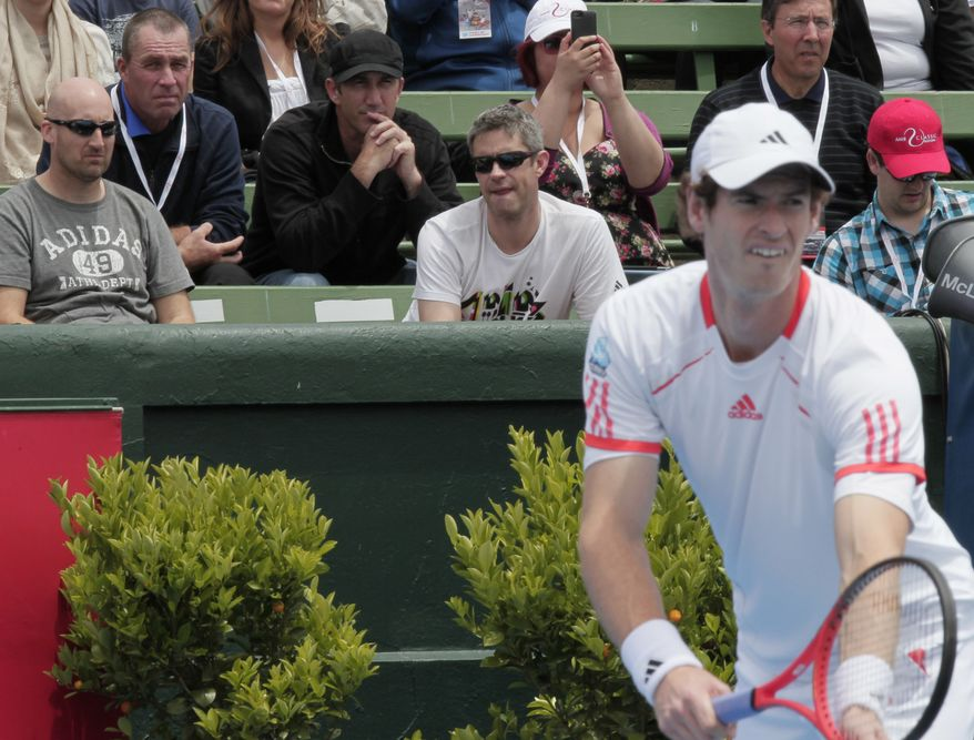Britain's Andy Murray prepares to serve as he is watched by his coach Ivan Lendl, top second left, and Darren Cahill during his exhibition match against Argentina's David Nalbandian at the Kooyong Classic in Melbourne, Australia, Friday, Jan. 13, 2012. (AP Photo/Mark Baker)