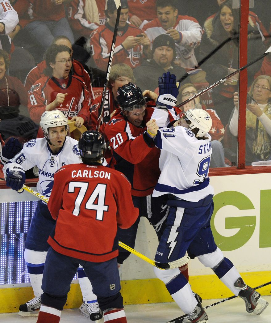 Tampa Bay Lightning center Steven Stamkos and Washington Capitals left wing Troy Brouwer  mix it up along the boards during the third period, Friday, Jan. 13, 2012, in Washington. (AP Photo/Nick Wass)
