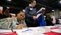 Mercedes Bagceci, an Army specialist, and her husband, Ismail, look over information for Ismail, who was among military spouses looking for work at the Military Spouse Career Forum and Hiring Fair at the Walter E. Washington Convention Center. (Andrew Harnik/The Washington Times)