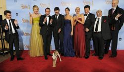 "The cast and crew of the film ""The Artist"" pose backstage with the award for Best Motion Picture - Comedy or Musical during the 69th Annual Golden Globe Awards Sunday, Jan. 15, 2012, in Los Angeles. From left, Thomas Langmann, Missy Pyle, Jean Dujardin, Uggie, Michel Hazanavicius, Berenice Bejo, Penelope Ann Miller, Ludovic Bource, Ken Davitian and James Cromwell. (AP Photo/Mark J. Terrill)"