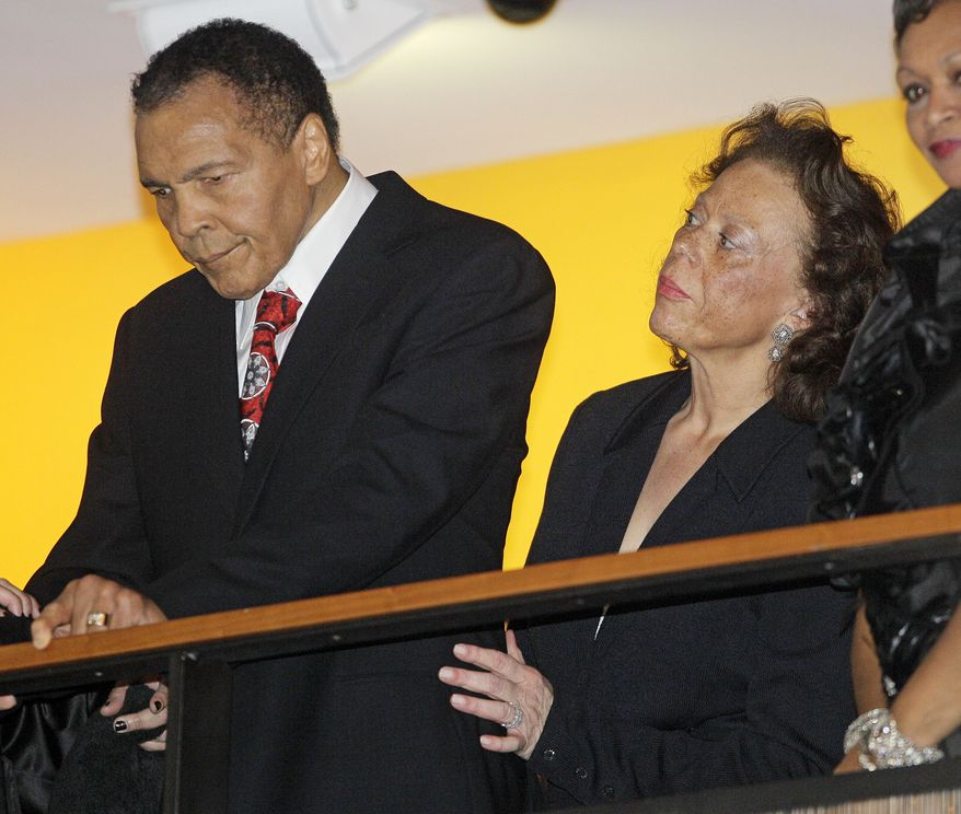 Boxing great Muhammad Ali is helped by his wife, Lonnie (right), as he looks down from a balcony at friends attending a celebration honoring his 70th birthday at the Muhammad Ali Center in Louisville, Ky., on Saturday, Jan. 14, 2012. He turned 70 on the following Tuesday. (AP Photo/Mark Humphrey)