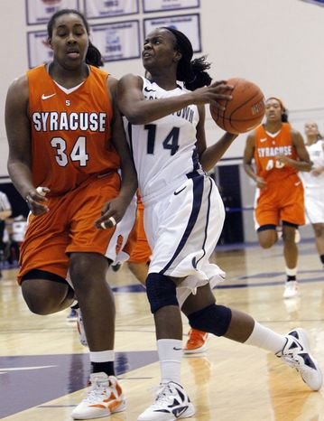 Georgetown guard Sugar Rodgers drives against Syracuse center Shakeya Leary during the second half of the game in Washington. Rodgers scored 21 points in Georgetown's 65-52 win on Saturday afternoon in Syracuse, N.Y. (AP Photo/Ann Heisenfelt)