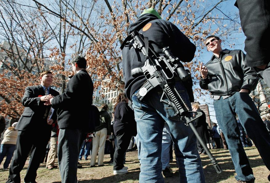 Some 200 people rallied on Capitol Square in Richmond Monday to push gun-friendly legislation, hours before a crowd occupied the same space to commemorate victims of gun violence. One participant in the pro-gun rally carries an AR-15 rifle slung over a shoulder. (Associated Press)