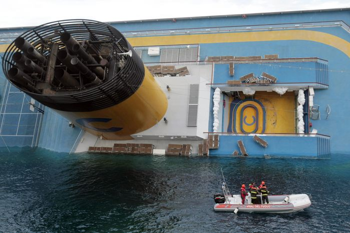 Italian firefighters scuba divers approach the cruise ship Costa Concordia leaning on its side, the day after it ran aground off the tiny Tuscan island of Giglio, Italy, Sunday, Jan. 15, 2012. A helicopter on Sunday airlifted a third survivor from the capsized hulk of a luxury cruise ship 36 hours after it ran aground off the Italian coast, as prosecutors confirmed they were investigating the captain for manslaughter charges and abandoning the ship. (AP Photo/Gregorio Borgia)