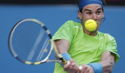 Spain's Rafael Nadal makes a backhand return to Alex Kuznetsov of the U.S. during their first round match at the Australian Open tennis championship, in Melbourne, Australia, Monday, Jan. 16, 2012. (AP Photo/Rick Rycroft)