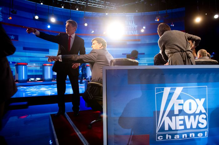 Republican Presidential hopeful Rick Perry speaks with Moderator Bret Baier of Fox News during a commercial break of a Presidential Debate at the Myrtle Beach Convention Center. (Andrew Harnik / The Washington Times)