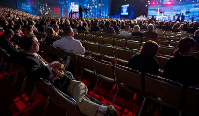 A boy lays down on the lap of a man in the audience as Republican presidential hopefuls Rick Perry, Rick Santorum, Mitt Romney, and Newt Gingrich speak at a Presidential Debate held by The South Carolina Republican Party, Fox News Channel, The Wall Street Journal, and Twitter at the Myrtle Beach Convention Center, Myrtle Beach, SC, Monday, January 16, 2012.(Andrew Harnik / The Washington Times)