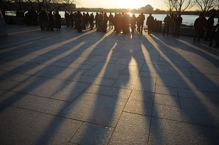 The shadows of people are seen in the early morning light as they arrive for the wreath-laying ceremony at the foot of the Stone of Hope at the Martin Luther King Jr. Memorial on the National Mall in Washington on Monday, Jan. 16, 2012. (Rod Lamkey Jr./The Washington Times)