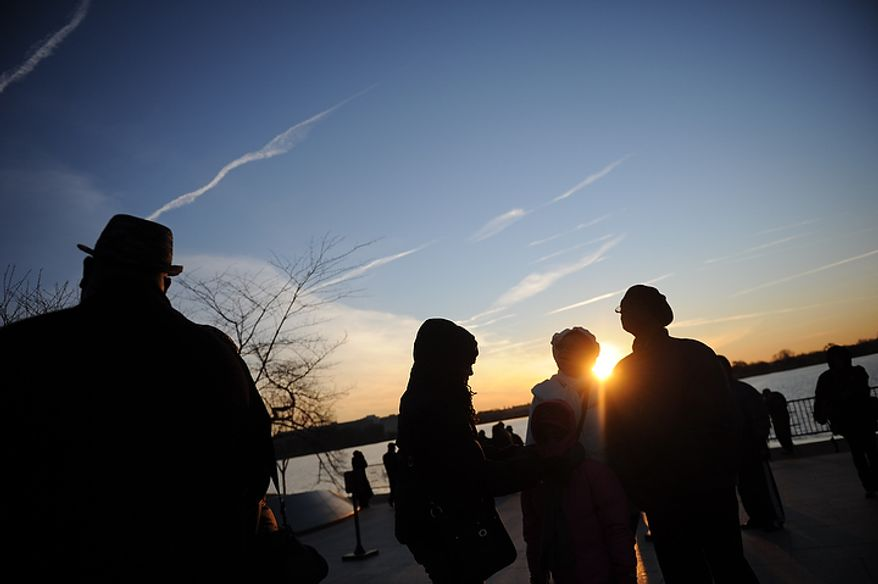 People arrive in the bitter cold at sunrise for the wreath-laying ceremony at the foot of the Stone of Hope at the Martin Luther King Jr. Memorial on the National Mall in Washington on Monday, Jan. 16, 2012. (Rod Lamkey Jr./The Washington Times)
