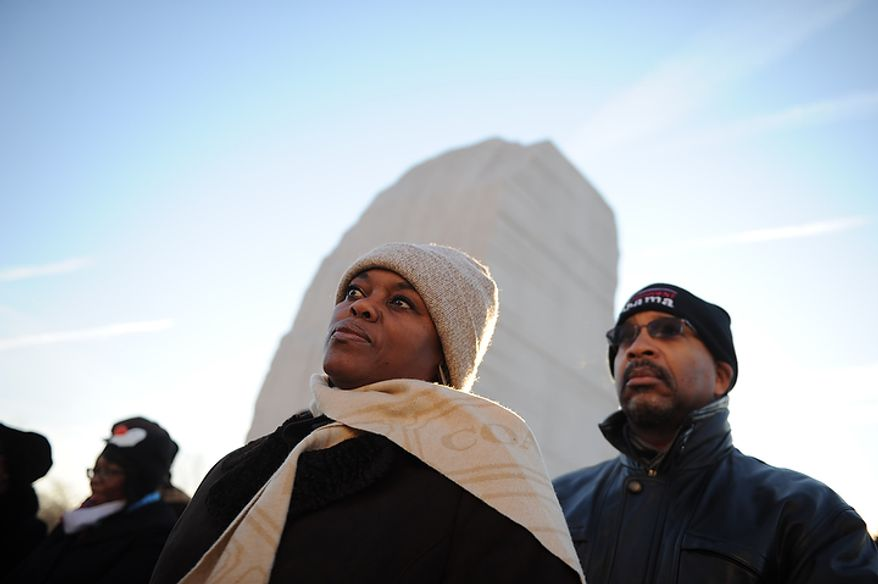 Mike Todd (right) and his wife, Sharon Pringle-Todd, of Alexandria watch as speakers offer remarks during the wreath-laying ceremony at the foot of the Stone of Hope at the Martin Luther King Jr. Memorial on the National Mall in Washington on Monday, Jan. 16, 2012. (Rod Lamkey Jr./The Washington Times)