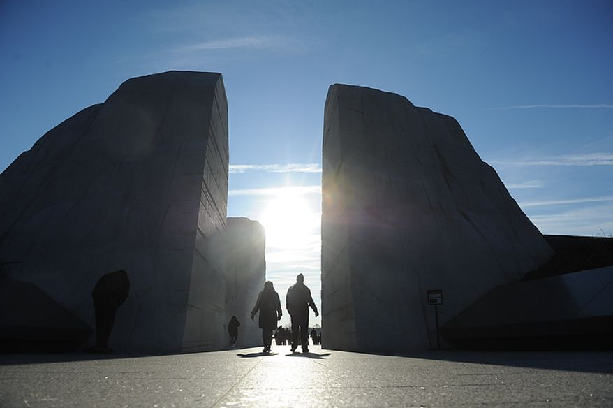 People are silhouetted by the early morning sun as they leave the Martin Luther King Jr. Memorial on the National Mall in Washington on Monday, Jan. 16, 2012. (Rod Lamkey Jr./The Washington Times)