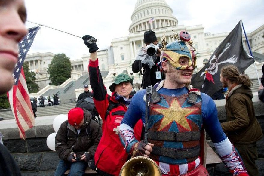 """A man who gave his name as """"King of America"""" jokes with the crowd during Tuesday's Occupy protest on the West Lawn Capitol while Rit Picone of New Paltz, N.Y., waves his upside-down American flag behind him. (Rod Lamkey Jr./The Washington Times)"""