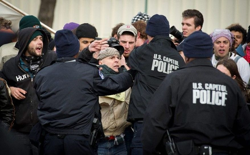 ** FILE ** Int his Jan. 17, 2012, file photo, U.S. Capitol Police attempt to arrest a man who crossed the police line during an Occupy protest on the West Lawn of Capitol. Other demonstrators pulled the man back into the crowd. (Rod Lamkey Jr./The Washington Times)