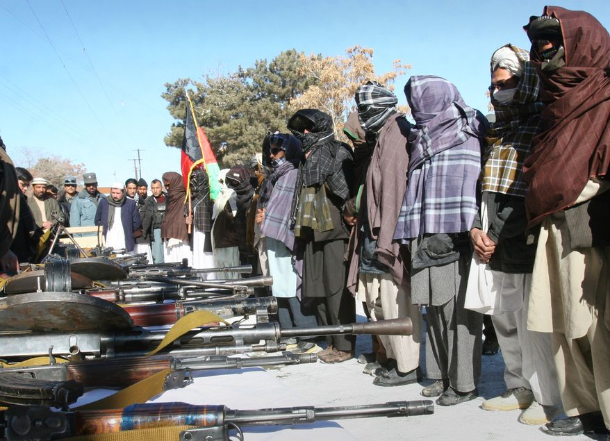 A former Taliban militant (center) holds the national flag of Afghanistan as other militants stand with faces covered during a joining ceremony with the Afghan government in Ghazni, west of Kabul, Afghanistan, on Monday, Jan. 16, 2012. About 25 former Taliban members handed over their weapons and joined with the Afghan government as part of a peace-reconciliation program. (AP Photo/Rahmatullah Naikzad)