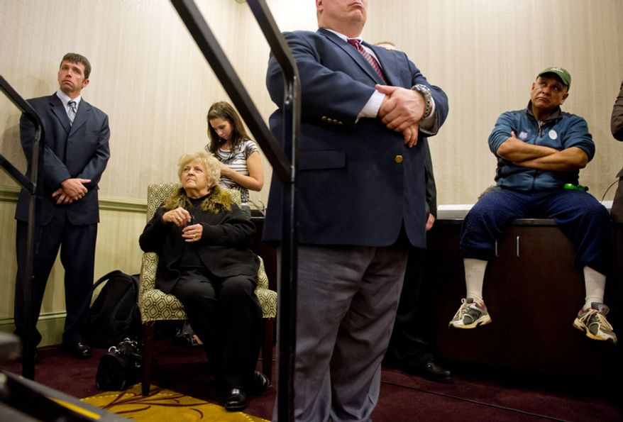 Carol Paul, second from left, is surrounded by security as she and Retired Army Staff Sgt. R.C. Acosta of Rock Hill, South Carolina listen to Republican presidential candidate Ron Paul speak during a campaign stop in Rock Hill, SC. (Andrew Harnik / The Washington Times)