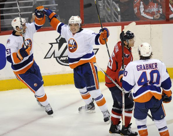New York Islanders right wing P.A. Parenteau, second from left, celebrates his goal with teammate Frans Nielsen (51) as Michael Grabner (40) approaches during the second period of an NHL game Tuesday, Jan. 17, 2012, in Washington. Washington Capitals center Jeff Halpern skates away. (AP Photo/Nick Wass)