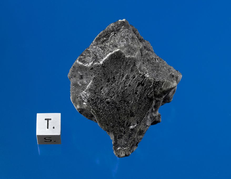 This handout photo provided by Darryl Pitt of the Macovich Collection shows an external view of a Martian meteorite recovered in December 2011 near Foumzgit, Morocco, following a meteorite shower believed to have occurred in July 2011. (Associated Press/Darryl Pitt, Macovich Collection)