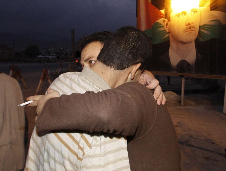 A freed Syrian prisoner (left) hugs a relative after being released from Adra Prison on the northeast outskirts of Damascus, Syria, on Monday, Jan. 16, 2012. SANA, the state news agency, said Sunday that President Bashar Assad had granted a general amnesty for crimes committed during the unrest of the past 10 months. (AP Photo/Muzaffar Salman)