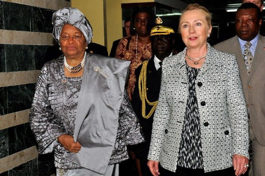 Liberian President Ellen Johnson Sirleaf, left, walks with U.S. Secretary of State Hillary Clinton at the Ministry of Foreign Affairs in Monrovia, Liberia Monday, Jan.16, 2012. Clinton was in Liberia to attend the second presidential inauguration of Sirleaf, Africa's first woman president, later in the day. (AP Photo/Abbas Dulleh)