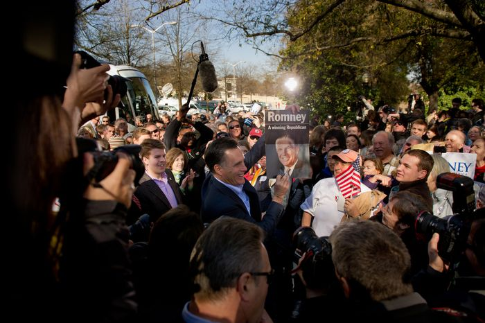 Republican presidential candidate and former Massachusetts Gov. Mitt Romney holds up an old campaign poster of his father George Romney, which a supporter handed him to sign during a campaign rally Jan. 18, 2012, on the Wofford College campus in Spartanburg,