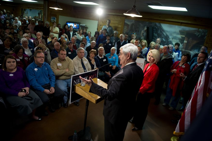 Republican presidential candidate Newt Gingrich speaks Jan. 18, 2012, at a town hall meeting at Mutt's BBQ in Easley, S.C. At his right is his wife Callista. (Andrew Harnik/The Washington Times)