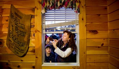 Nikki Rinkliff of Easley, S.C., leans in a window to take a photograph of Republican presidential candidate Newt Gingrich on Jan. 18, 2012, after a town hall meeting at Mutt's BBQ in Easley. (Andrew Harnik/The Washington Times)