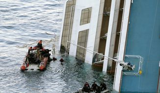 Italian naval divers (top left) recover a body from the cruise ship Costa Concordia on Tuesday, Jan. 17, 2012, off Italy's Tuscan coast. (AP Photo/Gregorio Borgia)