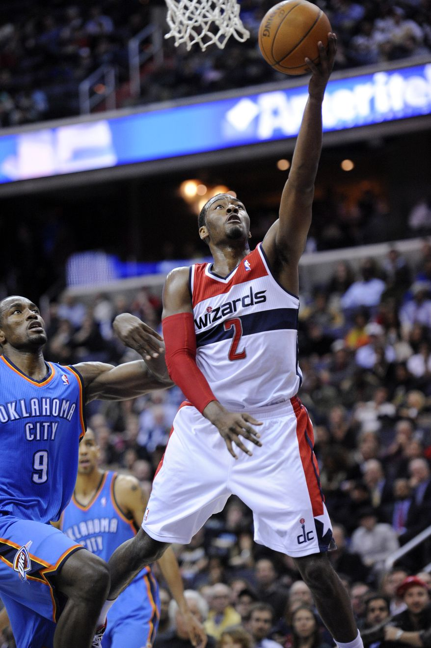 Washington Wizards guard John Wall goes to the basket against Oklahoma City Thunder forward Serge Ibaka during the second half Wednesday, Jan. 18, 2012, in Washington. The Wizards won 105-102. (AP Photo/Nick Wass)