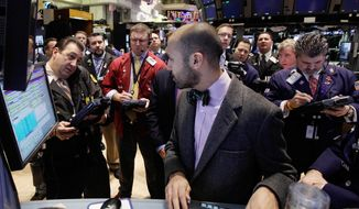 Specialist Fabian Caceres (foreground) works with traders at his post on the floor of the New York Stock Exchange on Wednesday, Jan. 18, 2012. (AP Photo/Richard Drew)