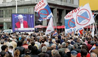 "Residents wave anti-EU flags as they watch a live broadcast from the U.N. court on the verdict for a key wartime Croatian commander, Gen. Ante Gotovina, in Zagreb, Croatia, in April. Croatia signed an EU accession treaty last year and is set to become a member in July 2013, if the Croats say ""yes"" in the referendum and all of the bloc's 27 states later ratify the deal. (Associated Press)"