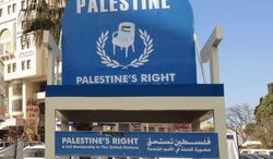 """A giant blue chair bearing the words """"Palestine's Right: Full Membership in the United Nations"""" sits in the central square of Ramallah in the West Bank, reinforcing Palestinians' ultimate goal to all who pass by. (Ben Birnbaum/The Washington Times)"""