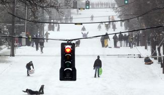 Sledders, skiers, snowboarders and pedestrians take over a snow-covered street in the Queen Anne neighborhood of Seattle on Wednesday, Jan. 18, 2012. (AP Photo/Elaine Thompson)