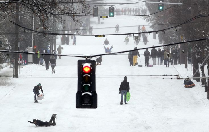 Sledders, skiers, snowboarders and pedestrians take over a snow-covered street in the Queen Anne neighborhood o