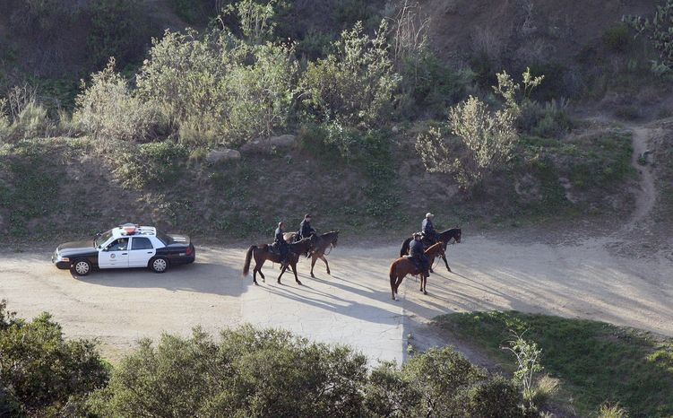 Mounted police officers search the Bronson Canyon area of Griffith Park in Los Angeles on Wednesday, Jan. 18, 2012, after a human head was discovered Tuesday by two people walking their dogs below the famous Hollywood sign. (AP Photo/Jason Redmond)
