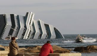 People view the cruise ship Costa Concordia as it lays on its side after running aground off the tiny Tuscan island of Giglio, Italy, Thursday, Jan. 19, 2012. (AP Photo/Gregorio Borgia)